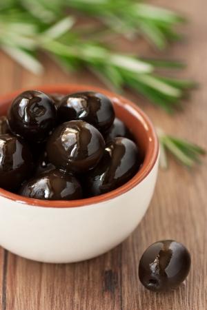 hoja de olivo: Las aceitunas y el romero en una mesa de madera. Foto de archivo