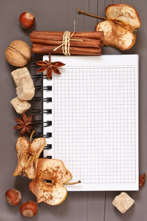 Notebook, nuts and spices on a rustic wooden board. photo