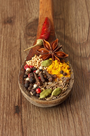 Colorful spices in a wooden spoon on the old table  photo