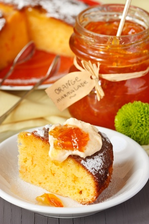 Sweet orange cake and jar of marmalade for breakfast. photo