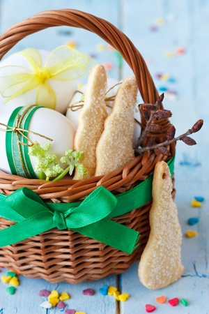 Easter bunny cookies, eggs with ribbon in a basket on an blue  wooden board  photo