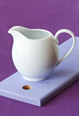 White milk jug on a blue wooden board. photo