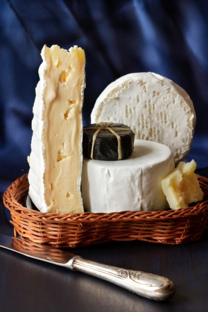 Assortment of cheese in a wicker basket. photo