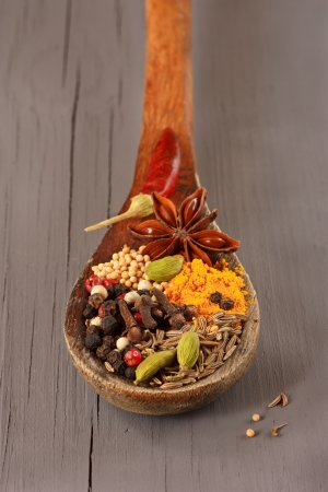 Colorful spices on an old wooden spoon. photo