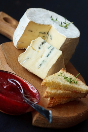 cheese board: Delicious cheese, cranberry jam and toasts on a wooden board