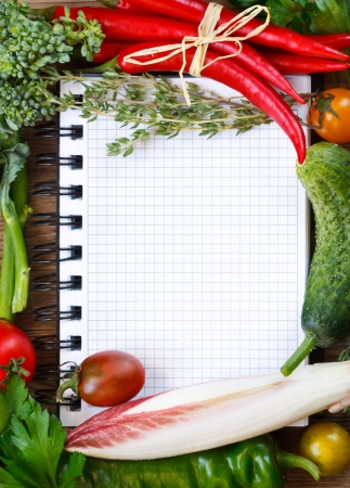 Beautiful vegetable frame notebook on a wooden board