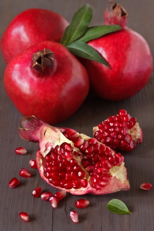 pomegranate juice: Fresh ripe pomegranates with leaves on an old wooden board.