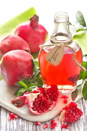 jugo de frutas: Jugo de granada casera y granadas maduras en una tabla de madera.