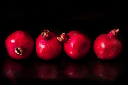 pomegranates: Ripe fresh pomegranates on a shiny black background. Stock Photo
