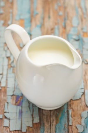 creamer: Jug of fresh milk on an old wooden board.