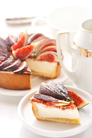 creamer: Delicious cheesecake with fresh figs on a white.