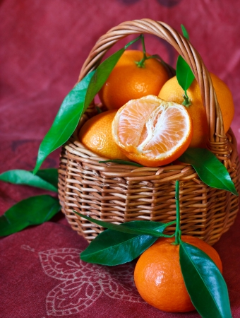 Sweet ripe mandarines with leaves in a wicker basket. photo