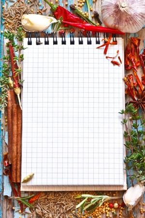 カラフルなスパイスとハーブ古い青い板に空ノートブックを開く 写真素材