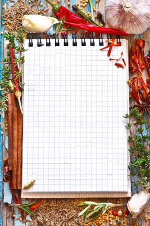 Open empty notebook with colorful spices and herbs on an old blue wooden board