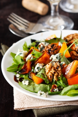 Delicious salad  Fresh arugula, persimmon, blue cheese and walnuts with balsamic vinegar  photo