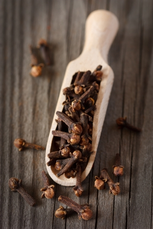 Spicy cloves in a wooden scoop on an old board  Stock Photo - 18005360