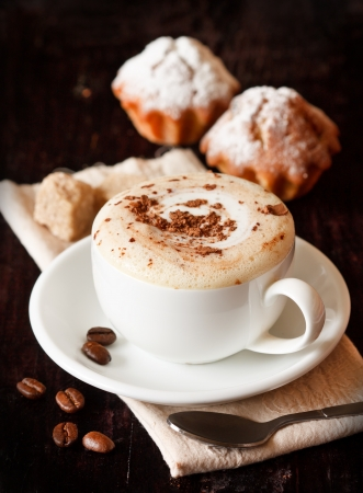 Cup of coffee with chocolate, coffee beans and muffins on a dark background  photo
