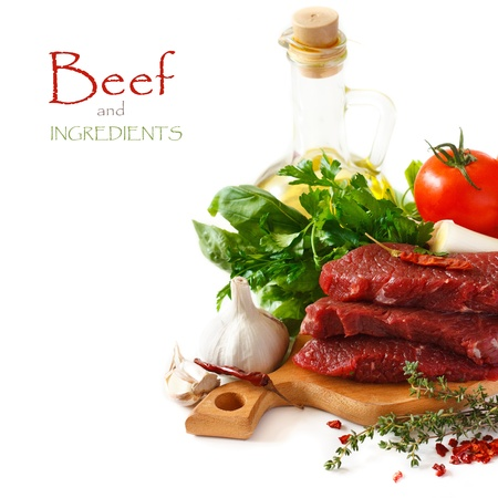 carne de res: Carne de vacuno cruda con especias y hierbas sobre un fondo blanco Foto de archivo