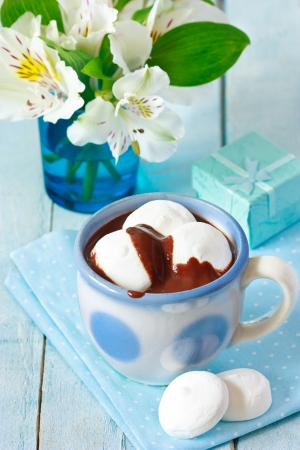 Cup of hot chocolate drink with marshmallow on a blue background  photo
