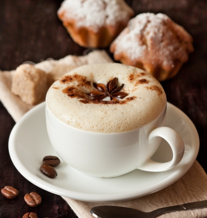 Cup of cappuccino and cake on a dark background close-up  photo
