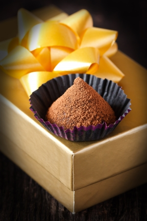 Homemade chocolate truffle in a paper case on a golden gift box. photo