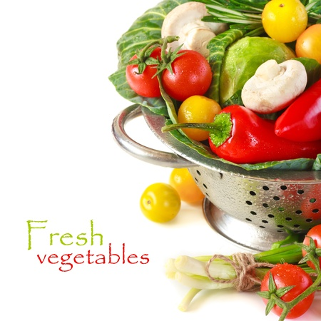 a colander: Fresh vegetables with water drops in a colander on a white