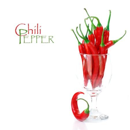 chiles picantes: Hot chili peppers en un vaso de vino sobre un fondo blanco Foto de archivo