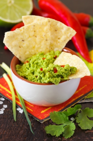 Fresh guacamole dip with nacho chips and ingredients