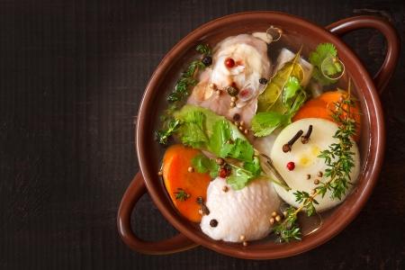 sopa de pollo: Caldo de pollo con verduras y especias en una olla de cerámica. Foto de archivo