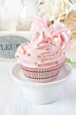strawberry cake: Sweet pink cupcake on a cake stand. Stock Photo