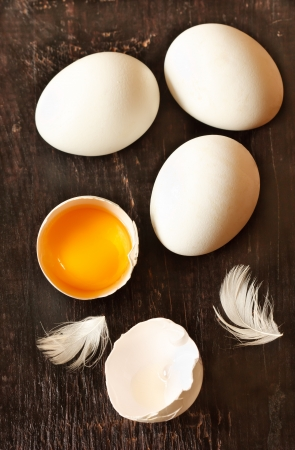 chicken egg: Fresh eggs with feather on a wooden background.