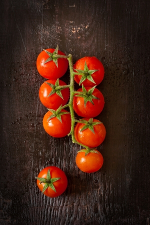 Fresh kitchen garden tomatoes on a wooden background.