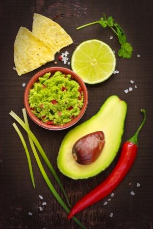aguacate: Ingredientes para la salsa guacamole y guacamole sobre un fondo oscuro