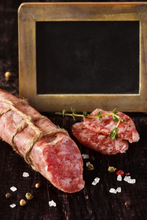 dark meat: Delicious salami sausage with thyme and spices and old chalk blackboard for price  Stock Photo