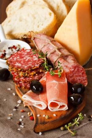 Ham, cheese and variety of salami with olives and spices on wooden board  Stockfoto