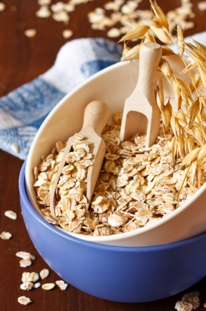 Oat flakes in a bowl with wooden scoop close up.