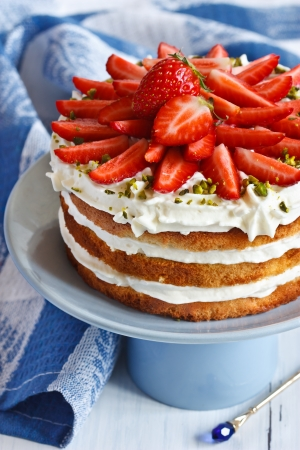 Sweet homemade cake with strawberry and whipped cream on a cake stand. photo