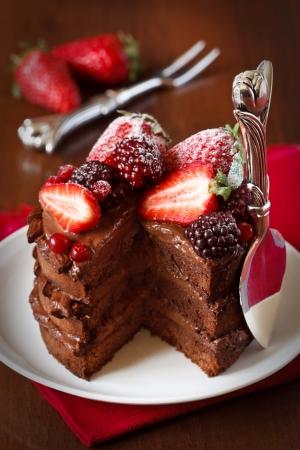 trozo de pastel: Delicioso pastel de chocolate con crema y bayas de cerca