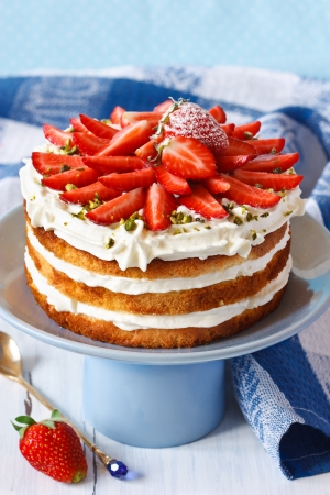Sweet homemade cake with strawberry and whipped cream on a cake stand.