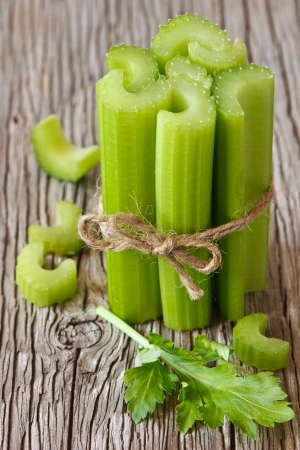 Bunch of fresh celery stalks on a wooden background.