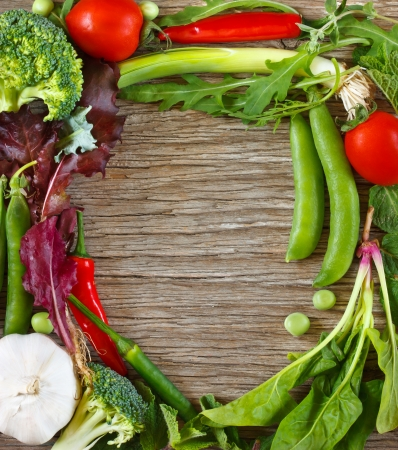 Frame of fresh vegetables and herbs on a wooden background  photo