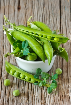 Fresh green peas with leaves in a white bowl. photo