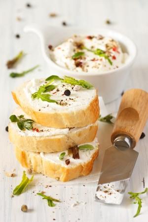 新鮮なクリーム チーズ朝食のスパイスとハーブ、カリカリのバゲットで 。