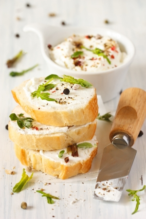 sandwich spread: Fresh cream cheese spread with spices and herbs on a crispy baguette for breakfast.