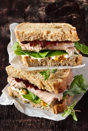 Delicious sandwich with meat, vegetables and mustard on a wooden background.