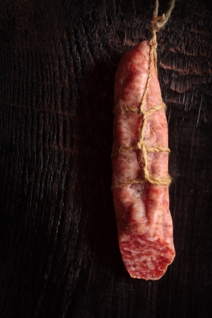 dark meat: Hanging salami sausage on an old wooden board.