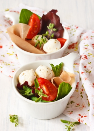 Delicious salad with ham and mozzarella cheese  photo