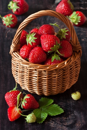 Sweet red strawberries in a wicker basket on an old wooden board. photo