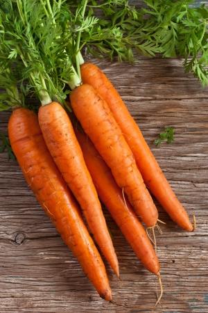 Bunch of fresh kitchen garden carrots on a wooden board.
