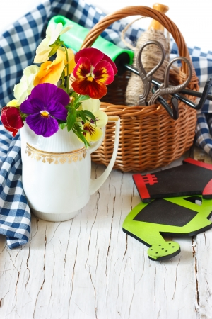Beautiful garden pansy flowers, garden tools and old basket on an old wooden board. photo